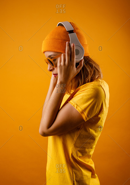 Happy young woman in bright clothes adjusting stylish sunglasses and smiling looking away while listening to music against orange background