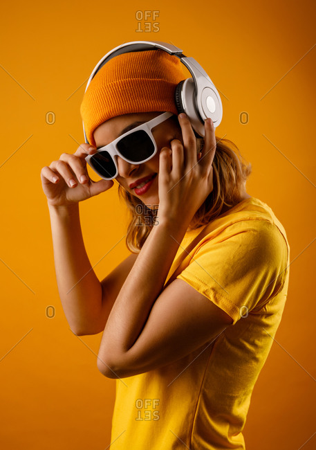 Happy young lady in bright clothes adjusting stylish sunglasses and smiling while listening to music against orange background