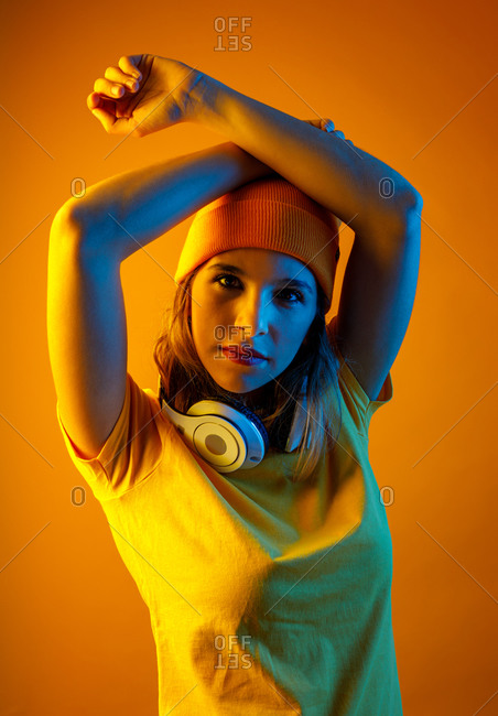 Confident stylish young woman in orange beanie with headphones around the neck keeping arm over head and looking at camera against orange background