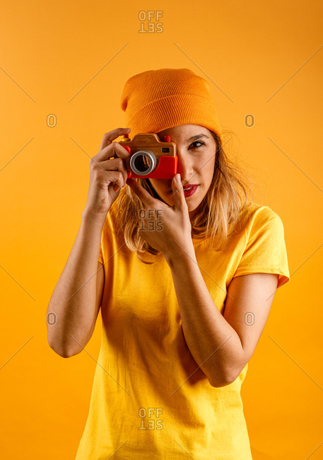 Happy young woman looking at camera while holding fake wooden vintage photo camera standing against yellow background