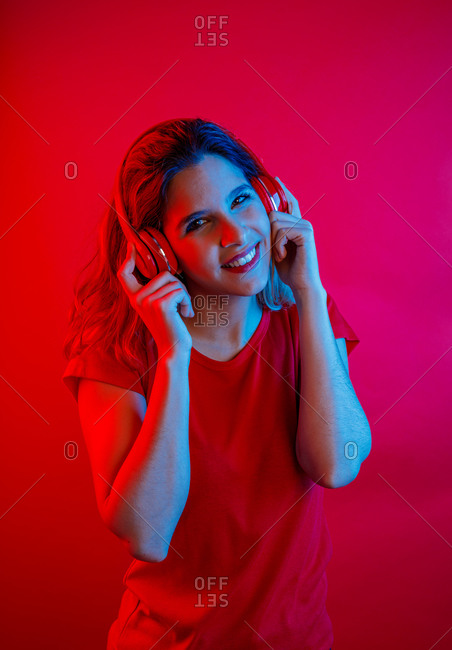 Happy young blonde woman in vivid headphones and t shirt smiling and looking at camera while listening to music against red background