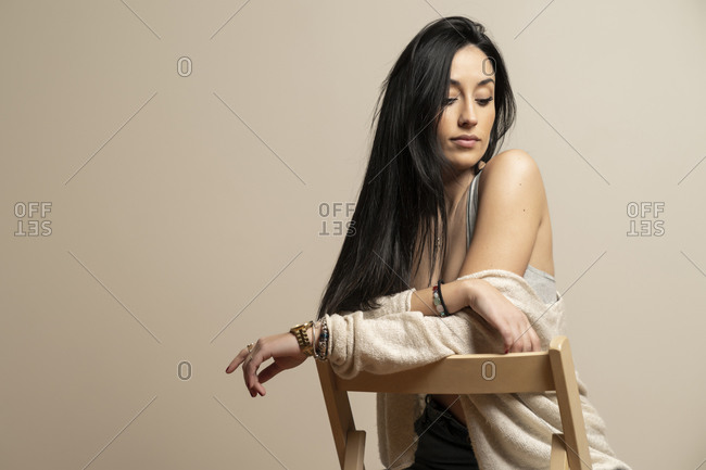 Brunette young female in casual clothes looking down sitting on chair against beige wall