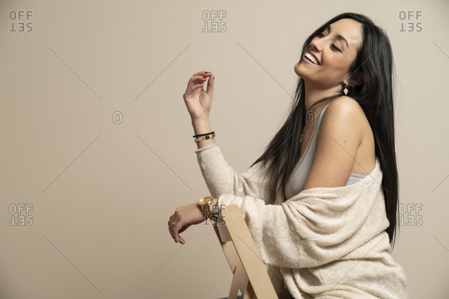 Side view of cheerful brunette young woman in casual clothes with closed eyes sitting on chair against beige wall