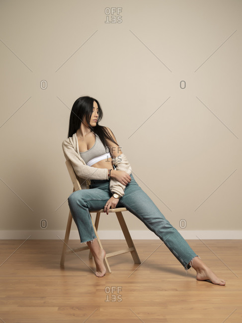 Full body slim brunette young female in casual clothes looking away while sitting on chair against beige wall