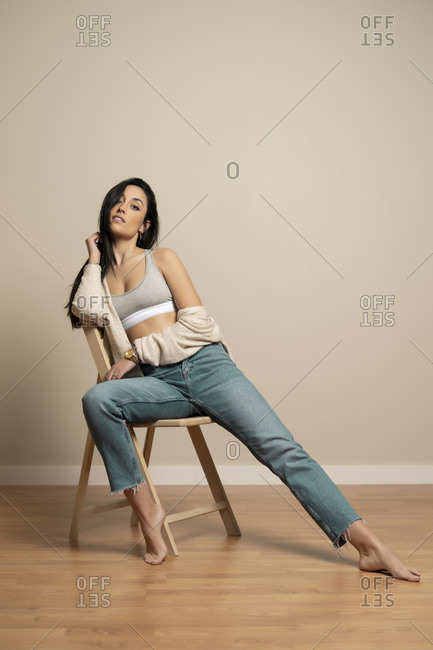 Full body slim brunette young female in casual clothes looking at camera while sitting on chair against beige wall