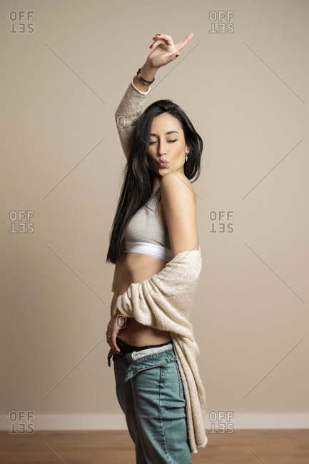 Side view slim brunette young female in casual clothes with closed eyes, pouting kiss with lips and raising arm standing against beige wall