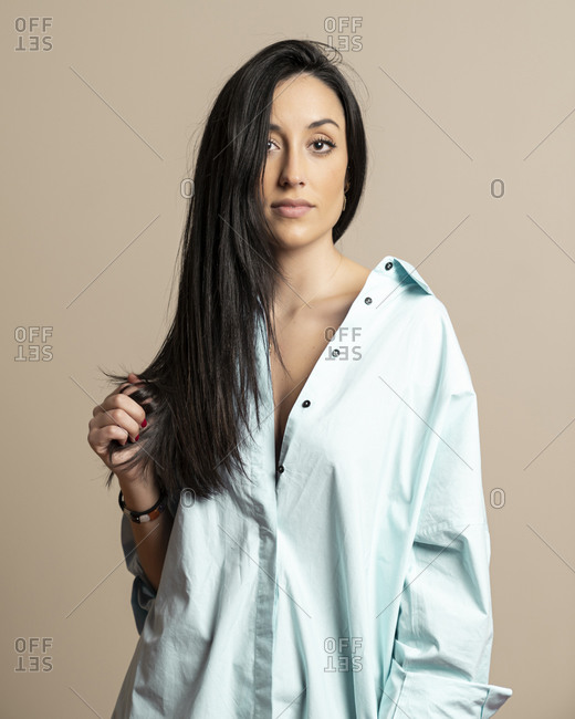 Beautiful brunette young female in casual blue shirt looking at camera standing against beige wall