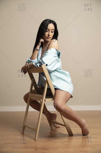 Full body side view of slim brunette young female in blue shirt looking down with closed eyes sitting on chair against beige wall