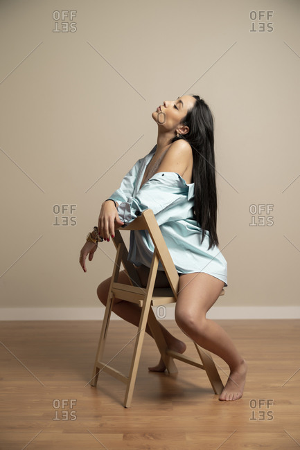 Full body side view of slim brunette young female in blue shirt with closed eyes sitting on chair against beige wall