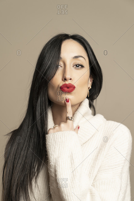 Attractive brunette woman model in stylish sweater looking at camera while pouting red lips and poking chin against beige background