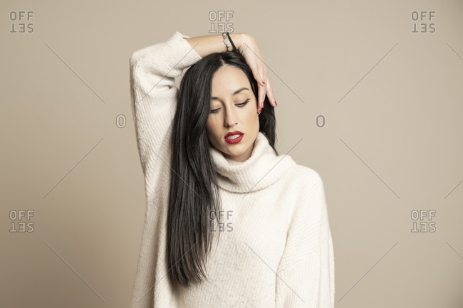 Attractive brunette woman model in stylish sweater with closed eyes holding hair against beige background