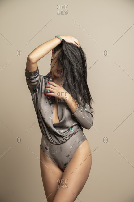 Unrecognizable attractive brunette woman model in stylish body holding had with hair covering face against beige background
