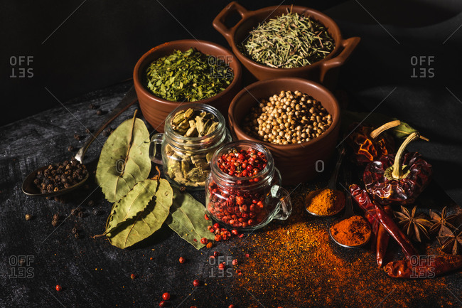 From above composition with different kinds of natural aromatic spices placed on slate surface background