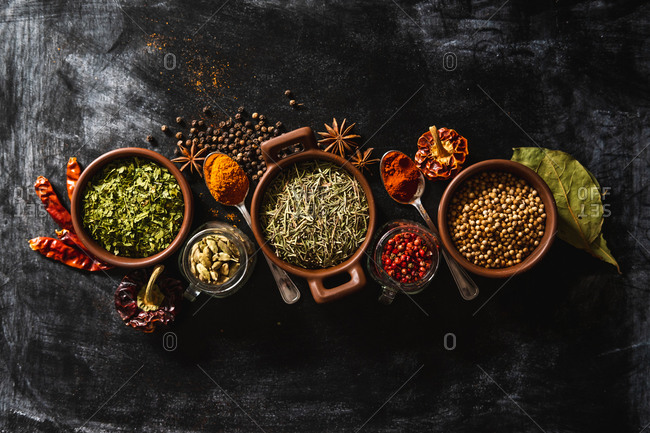 Top view composition with different kinds of natural aromatic spices placed on slate surface background