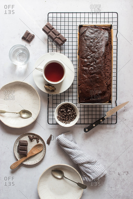 From above yummy banana and chocolate cake and cup of fresh tea placed on table near ingredients and dishware