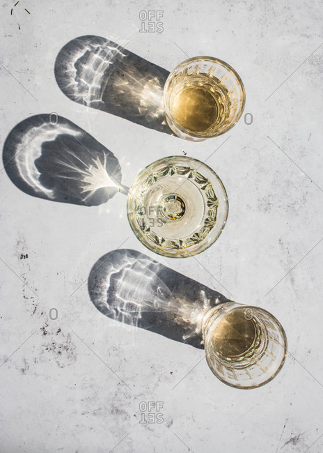 Top view composition of various glasses with alcohol drinks in sunlight leaving shadows and lights on marble surface
