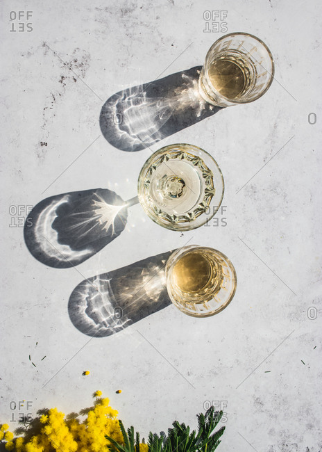 Top view composition of various glasses with alcohol drinks in sunlight leaving shadows and lights on marble surface with yellow flowers
