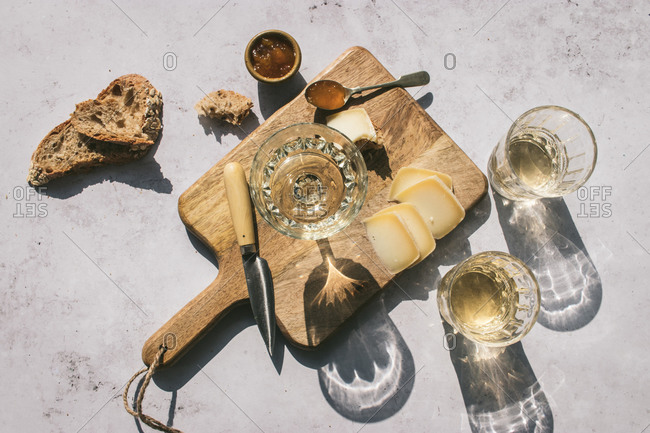 Top view composition with glasses of wine served with sliced cheese and bread with jam on marble table with wooden board in sunlight
