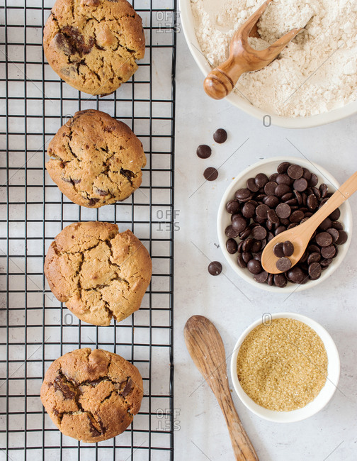 Top view of delicious freshly baked homemade cookies with chocolate chips placed on kitchen grid near bowls with ingredients