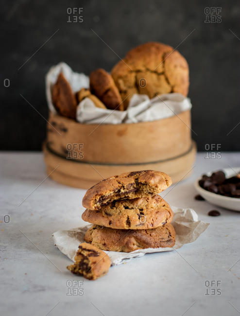 Stack of yummy chocolate chip cookies with bitten piece placed on table near wooden bowl with fresh homemade pastry