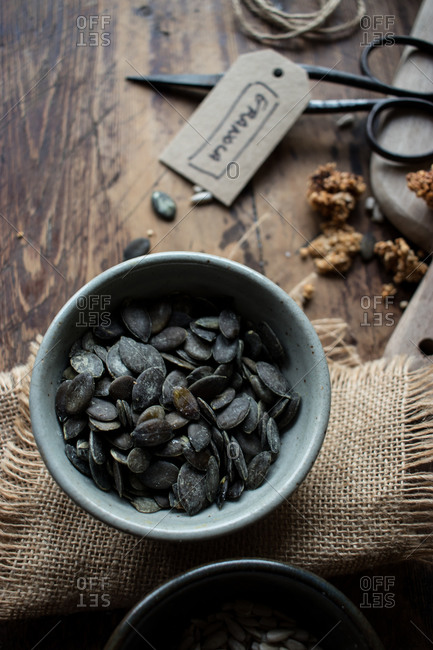 Top view of bowl of black pumpkin seeds placed on linen napkin near retro scissors and granola tag