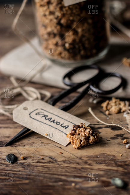 Closeup piece of fresh millet and quinoa granola placed on lumber table near vintage scissors and paper label