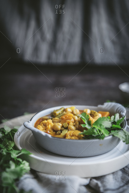 Bowl with tasty chickpea curry and herbs placed near gray cloth napkin in rustic setting