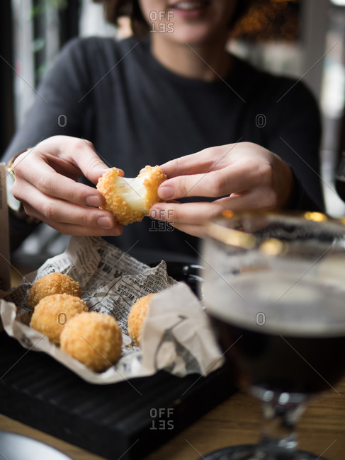 Crop unrecognizable smiling female holding delicious cheese ball with mozzarella filling while sitting at table in cafe