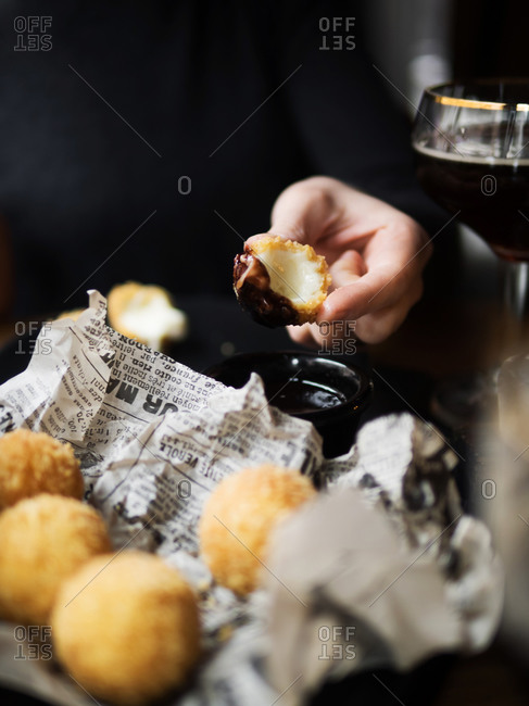 Crop unrecognizable female holding delicious cheese ball with mozzarella filling while sitting at table in cafe
