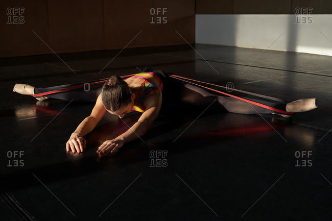 Unrecognizable professional ballet dancer lying down on the floor with elastic band stretching warming up during rehearsal on a modern dark academy studio