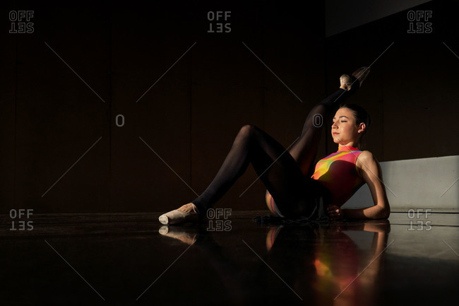 Side view of professional ballet dancer lying down on the floor stretching warming up during rehearsal on a modern dark academy studio