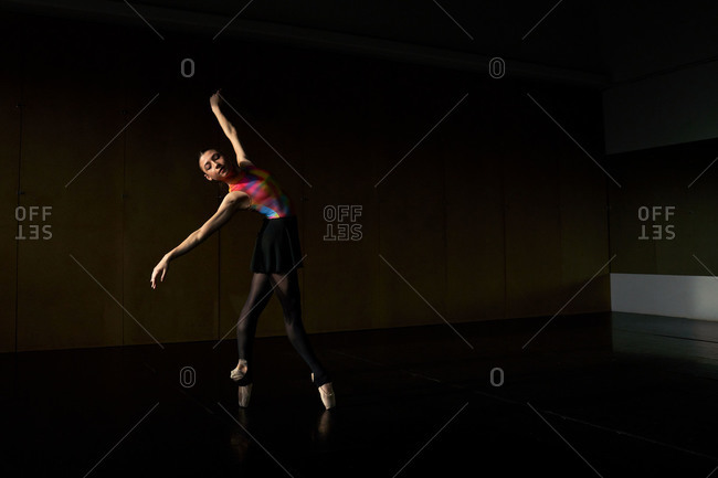 Professional ballet dancer dancing with closed eyes bending back while warming up during rehearsal on a modern dark academy studio