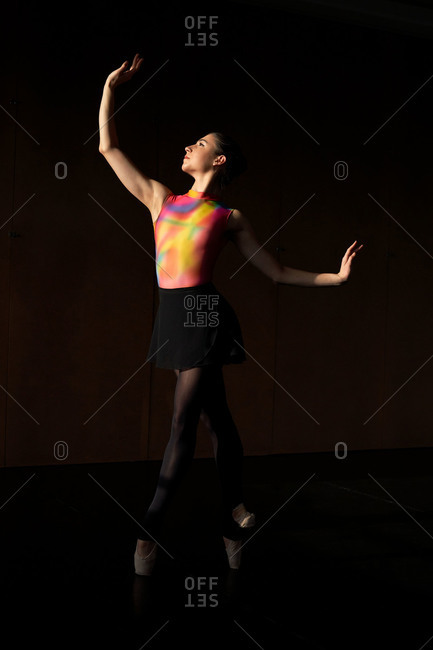 Professional ballet dancer dancing looking up while warming up during rehearsal on a modern dark academy studio