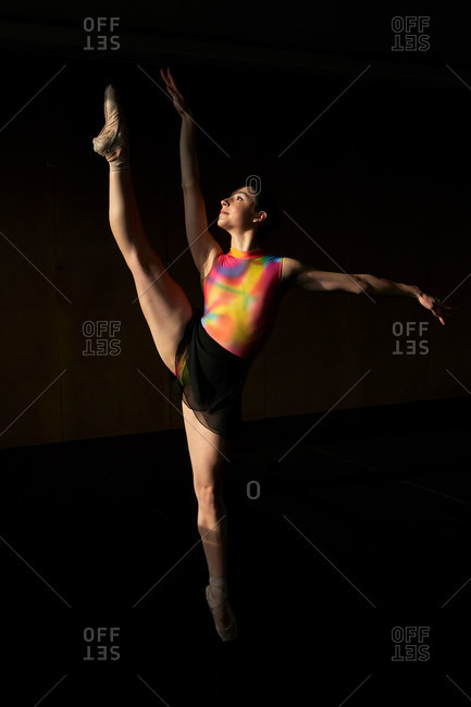 Professional ballet dancer dancing with leg up while warming up during rehearsal on a modern dark academy studio