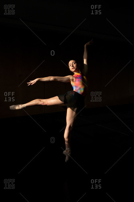 Professional ballet dancer dancing jumping with closed eyes while warming up during rehearsal on a modern dark academy studio