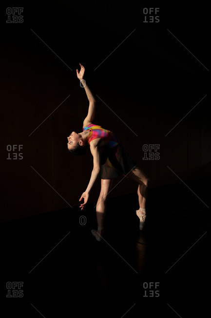 Professional ballet dancer dancing looking up bending back while warming up during rehearsal on a modern dark academy studio