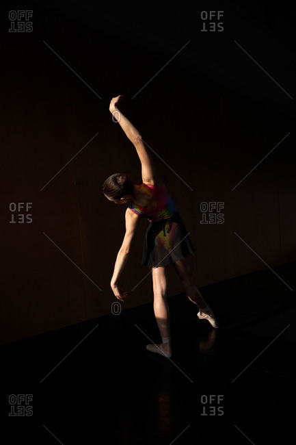 Back view of unrecognizable professional ballet dancer dancing with closed eyes while warming up during rehearsal on a modern dark academy studio