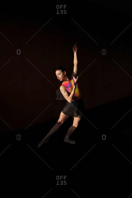 Professional ballet dancer dancing with closed eyes while warming up during rehearsal on a modern dark academy studio