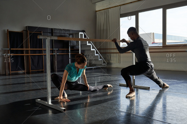Interracial couple of professional ballet dancers training in a modern studio using wooden handrail