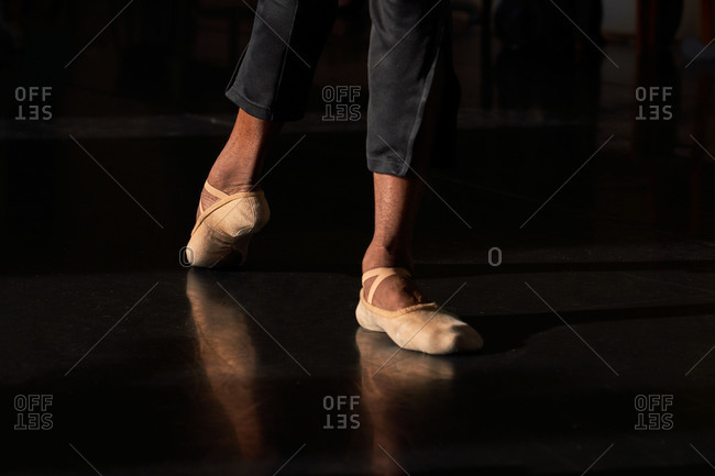 Unrecognizable crop professional ballet dancer foot on tiptoe wearing pointe ballet shoes in a modern studio