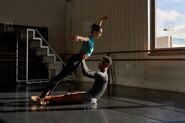 Interracial couple of professional ballet dancers looking at each other while training near big windows in a modern studio