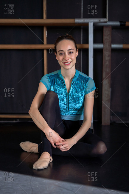 Happy professional ballet dancer sitting on the floor looking at camera resting after dancing training on a modern dark academy studio