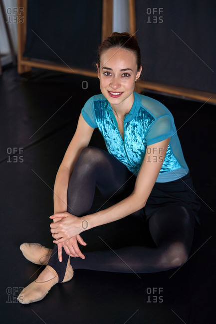 From above happy professional ballet dancer sitting on the floor looking at camera resting after dancing training on a modern dark academy studio