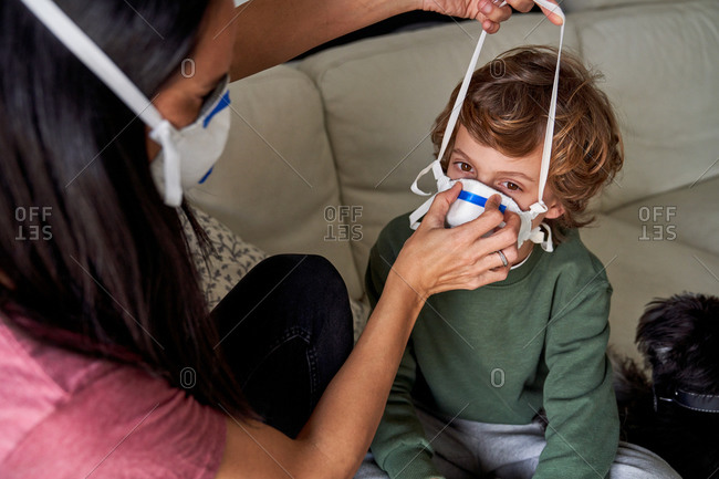 Mother putting on a respirator for her child to avoid possible infection