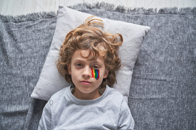 From above boy with bright rainbow under eye lying on pillow and blanket and looking at camera while staying home during quarantine