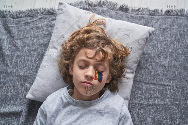 From above cute boy in pajama and with rainbow under eye lying on pillow and blanket and sleeping while staying home during quarantine