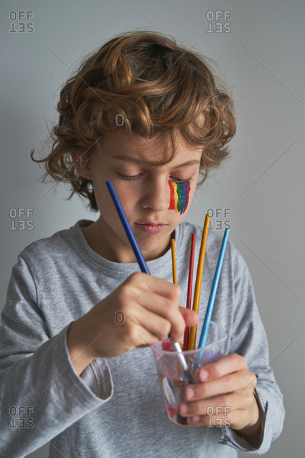 Focused boy with rainbow on face washing brush in cup of water while standing against gray background and painting during quarantine