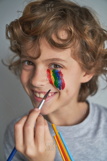 Happy boy painting colorful rainbow under eye and looking at camera while staying home during pandemic