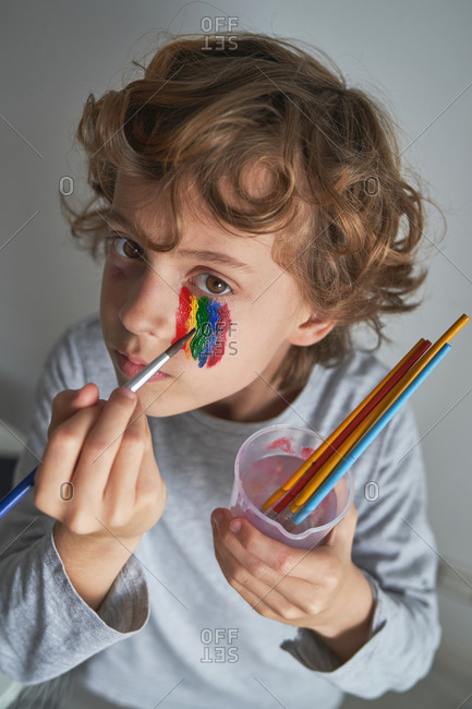 From above unhappy boy painting colorful rainbow under eye and looking at camera while staying home during pandemic