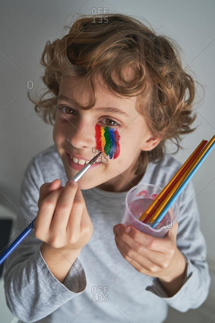 From above happy boy painting colorful rainbow under eye and looking at camera while staying home during pandemic